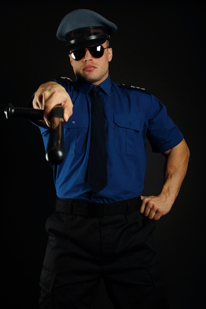 nightstick: Muscular policeman shows on you with nightstick on dark background