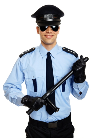 Smiling young policemen in uniform holds nightstick at hands photo
