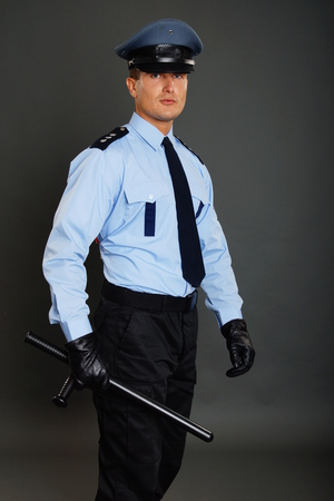 nightstick: Young policeman in uniform holds nightstick on gray background