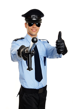 Young smiling policeman in sunglasses shows you thumbs up photo