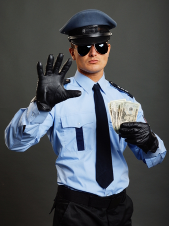 Policeman in uniform shows you stop with leather glove and holds money