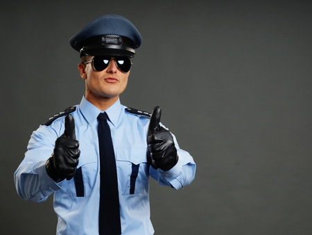 Young policeman in uniform shows you thumbs up