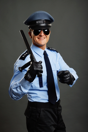 Smiling policeman in uniform with nightstick shows on you with his finger