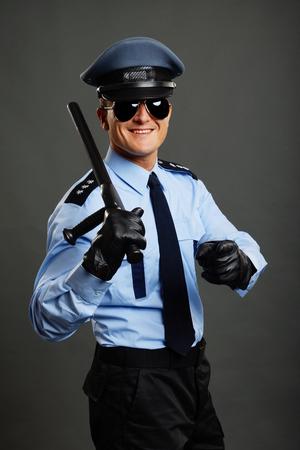 Lächelnd Polizist in Uniform mit Knüppel zeigt auf Sie mit dem Finger Standard-Bild - 30441102