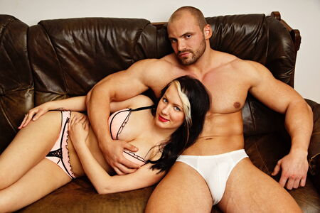 Muscular man sitting on leather couch with his girlfriend photo