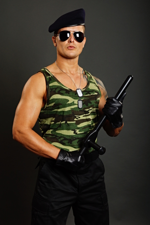 nightstick: Young military man at sunglasses poses with nightstick