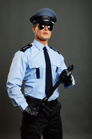 Young policeman in uniform poses with nightstick on gray background