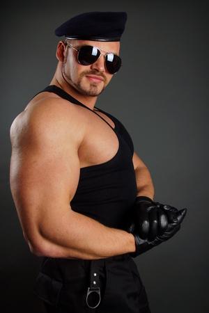 militaire sexy: Soldat musculaire dans les gants de cuir montre ses biceps Banque d'images