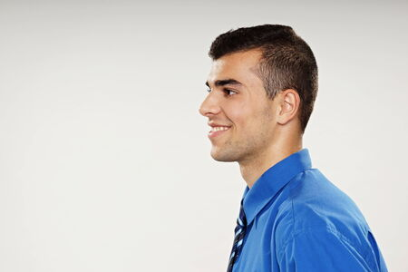 Profile of smiling young man in blue shirt, left you can write some text Stock Photo