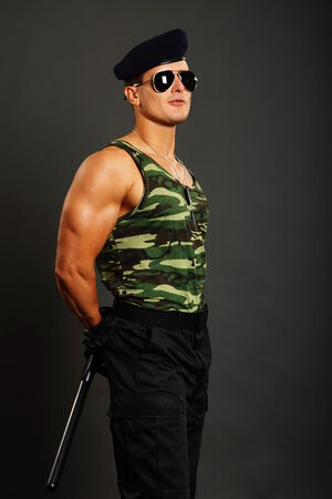 nightstick: Standing young military man at sunglasses with nightstick on gray background