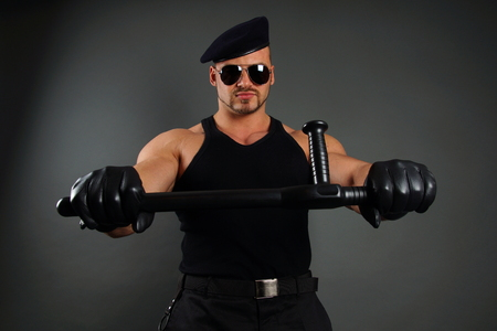 nightstick: Muscular soldier in leather gloves holds nightstick Stock Photo