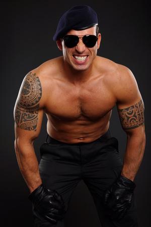 militaire sexy: Angry soldat muscl� en montrant ses dents sur fond sombre