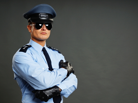 Portrait of policeman in sunglasses gray background Foto de archivo