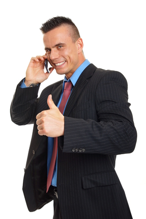 Smiling young man talks into mobile phone and shows thumb up