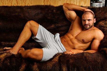 hombre deportista: Hombre musculoso acostado en el sofá y se relaja Foto de archivo