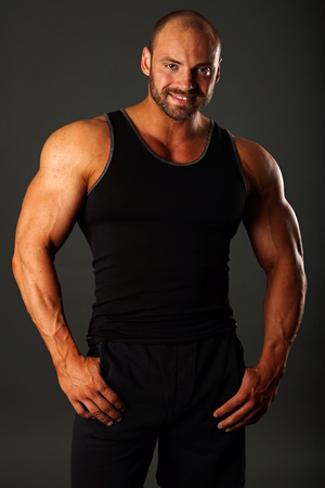 hombre deportista: Hombre muscular en camisa de color negro de pie sobre fondo gris