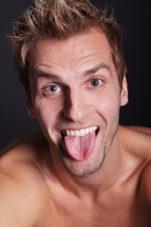 tongue: Young crazy man sticks out his tongue Stock Photo