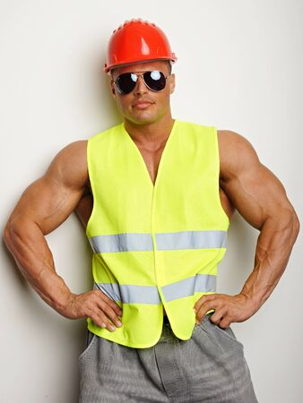 Muscular builder in sunglasses with a protective helmet