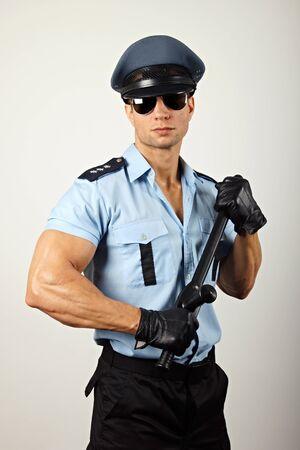 Portrait of policeman in sunglasses holding nightstick Standard-Bild