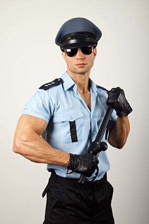 nightstick: Portrait of policeman in sunglasses holding nightstick Stock Photo