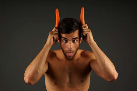 muscle guy: Young crazy man sticks out tongue devil with horns carrots on the head Stock Photo