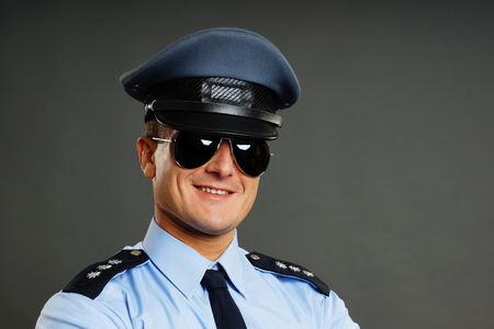 policeman: Portrait of smiling policeman in sunglasses on the gray background