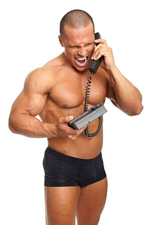 yells: Angry muscular man yells into the phone Stock Photo
