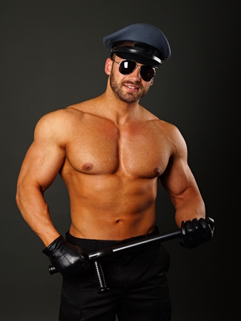 nightstick: Muscular policeman in sunglasses holds police nightstick on gray background
