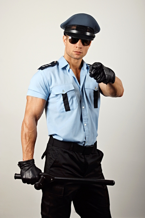 Portrait of policeman in sunglasses holding nightstick and shows on you Standard-Bild