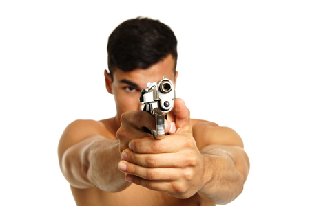gun barrel: Young man pointing a gun in hand on white background, focus is on gun barrel Stock Photo