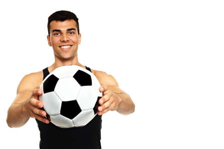 undershirt: Young man in black undershirt holds soccer ball, focus is on ball