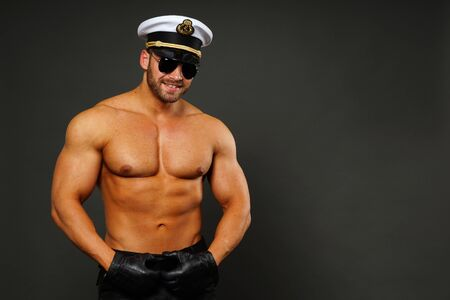 model male: Portrait of muscular man - captain with sunglasses on gray background, right you can write some text