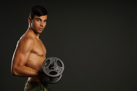 model male: Muscular young man exercises and poses with dumbbell on gray background, right you can write some text