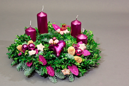 Beautiful advent wreath with four violet candles on gray background