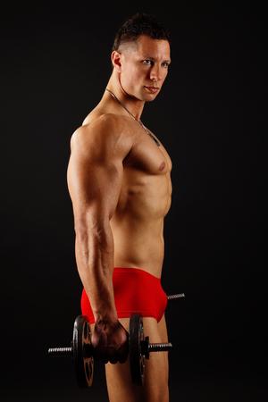 modelos hombres: Hombre joven muscular en boxer rojo ejercicios con pesas en el fondo oscuro