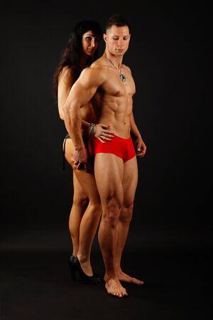 modelos hombres: Poses musculares con su novia sobre un fondo oscuro Foto de archivo