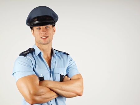 Portrait of smiling muscular policeman in police cap, you can write some text in right