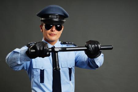 nightstick: Policeman in uniform holds police nightstick on gray background