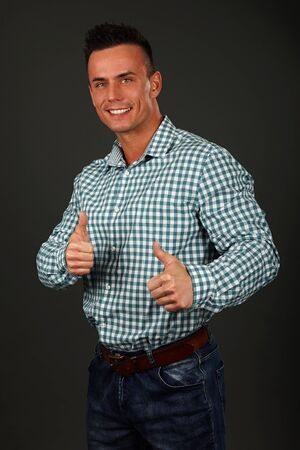 Smiling young man standing shows you thumbs up