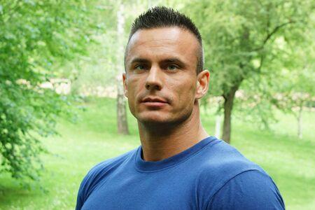 Portrait of handsome man in blue shirt at the park Standard-Bild