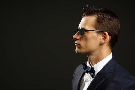 Profile of young businessman in suit on gray background with sunglasses, left you can write some text Standard-Bild