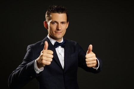 Young businessman in suit shows you thumbs up on gray background Standard-Bild