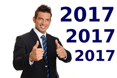 Handsome smiling businessman in suit shows you thumbs up with for Happy new year 2017