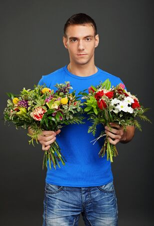 Young man holds two bouquet different flowers on gray background