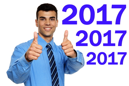 Young smiling businessman in blue shirt shows you thumbs up for Happy new year 2017