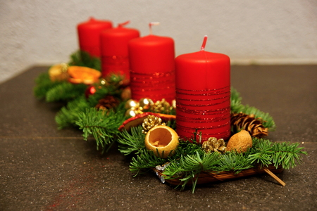 Advent decoration with four red candles and spruce branch