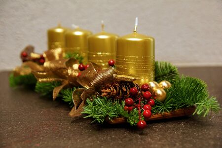 Advent decoration with gold candles and spruce branch