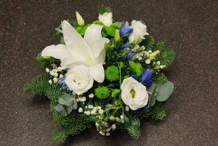 Christmas decoration with spruce branch, white lily, rose and blue bells