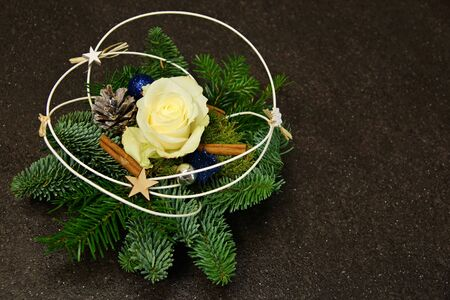 Christmas decoration with cone, spruce branches and flower rose