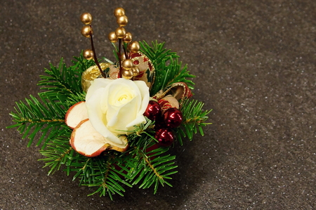 Christmas decoration with spruce branches and rose on gray background